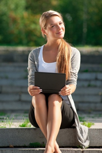 Young business woman sitting on stairs and using laptop outdoors